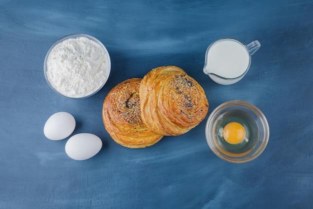 Dois deliciosos pastéis tradicionais com farinha e leite na superfície azul.