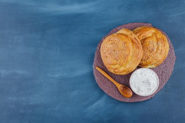 Dois deliciosos pastéis tradicionais e creme de leite na peça de madeira.