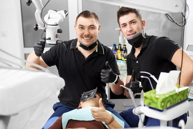 Dois dentistas mostrando os polegares