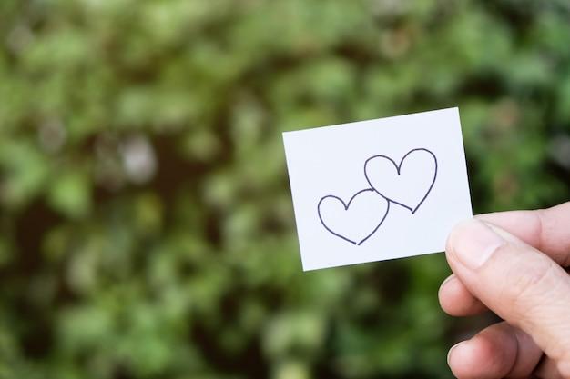 Dois desenhos de coração no papel. tem um fundo de árvore verde.