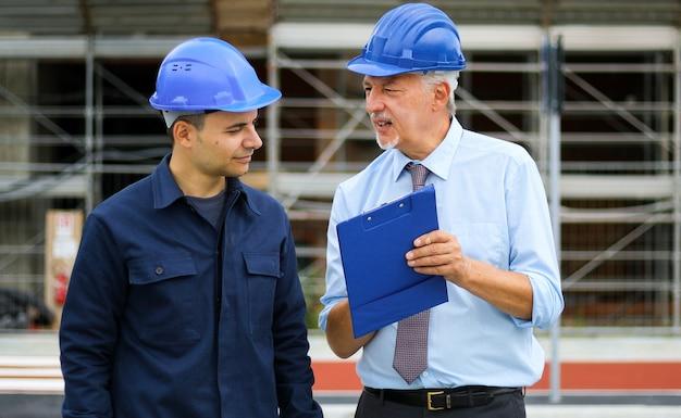 Dois desenvolvedores arquitetos revisando os planos de construção no canteiro de obras
