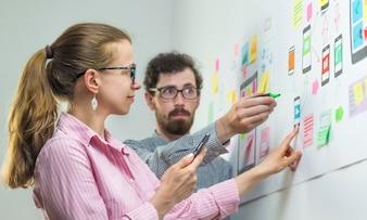 Dois designers criativos desenvolvem aplicativos móveis no local de trabalho.