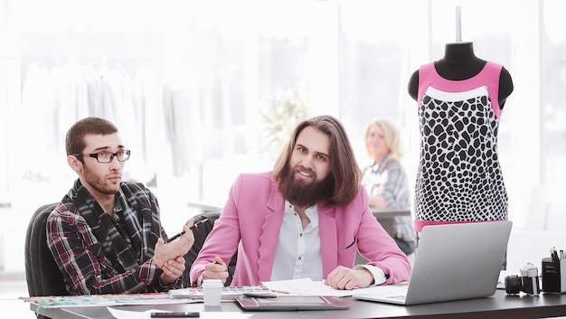 Dois designers de moda discutindo os designs dos novos modelos.
