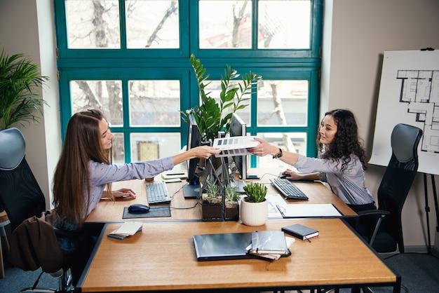 Dois designers femininos caucasianos, trabalhando no escritório moderno. uma garota dá paleta de cores para outra.