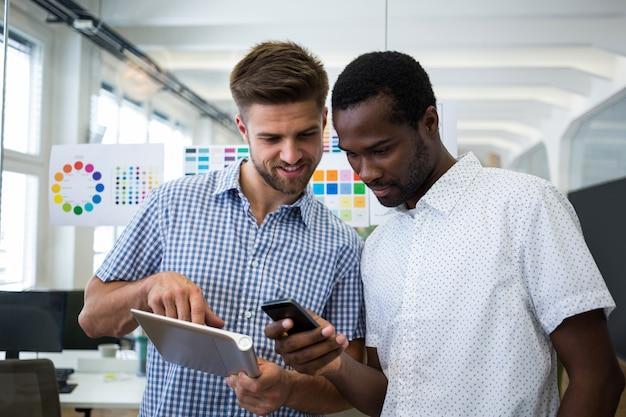 Dois designers gráficos do sexo masculino que usa a tabuleta digital e telefone celular