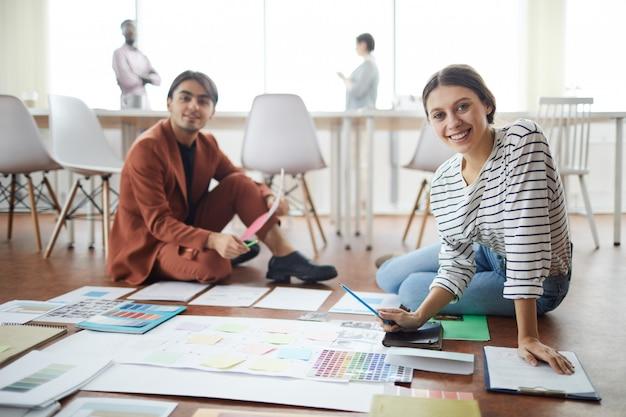 Dois designers planejando projeto no chão