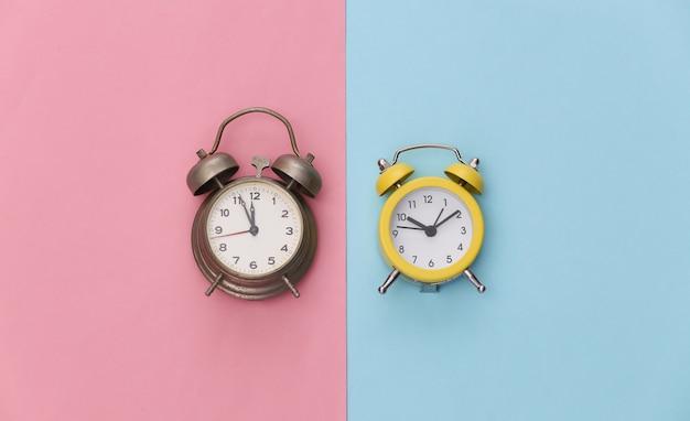 Dois despertadores em fundo rosa azul pastel.