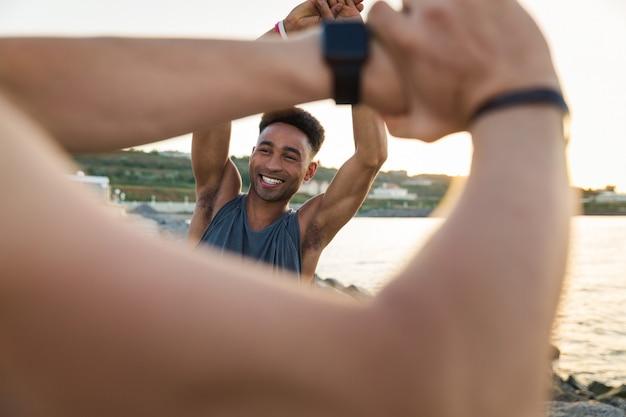 Dois desportistas jovens sorridentes a aquecer