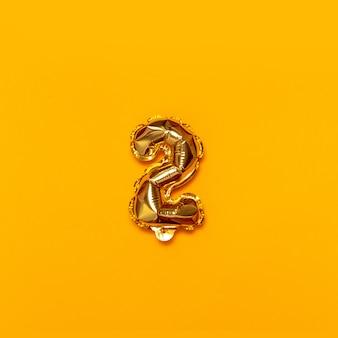 Dois dígitos dourados voam no ar em um fundo monofônico amarelo.