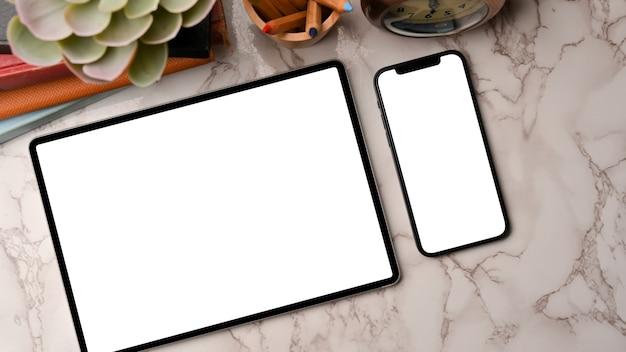 Dois dispositivos em layout plano, tablet inteligente e maquete de smartphone em fundo de mármore