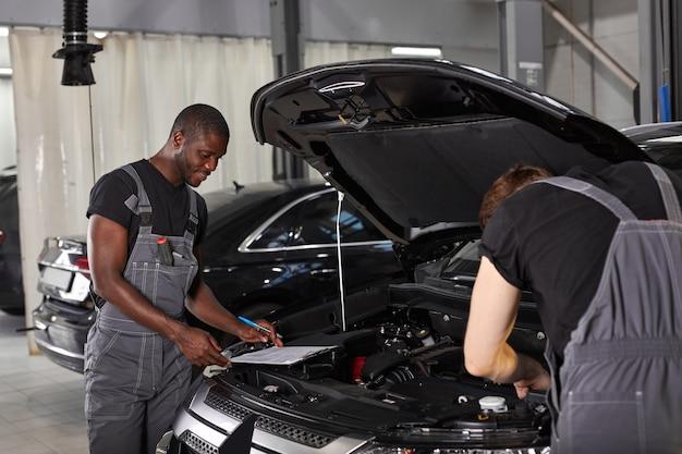 Dois diversos mecânicos de automóveis cooperando enquanto examinam o motor do carro
