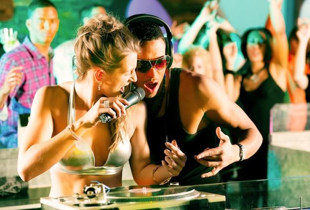 Dois djs na plataforma giratória no clube