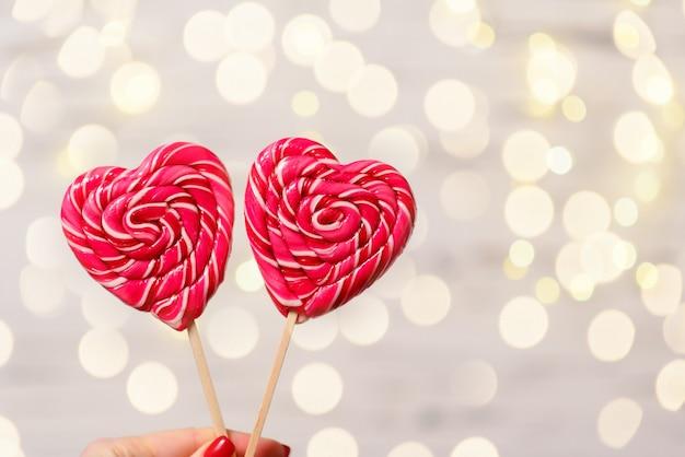 Dois doces coloridos em forma de coração no bokeh de fundo, close-up. o conceito de dia dos namorados.