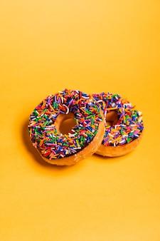 Dois donuts com cobertura de chocolate e granulado no fundo amarelo com espaço de cópia