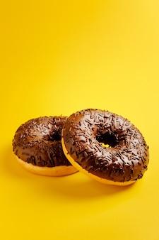Dois donuts de chocolate em fundo amarelo