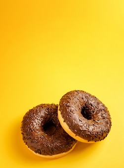 Dois donuts de chocolate na vista superior do fundo amarelo
