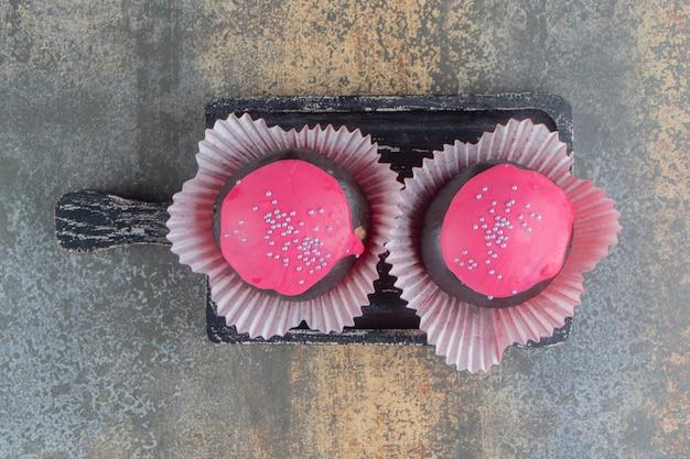 Dois donuts doces de chocolate com cobertura rosa e granulado