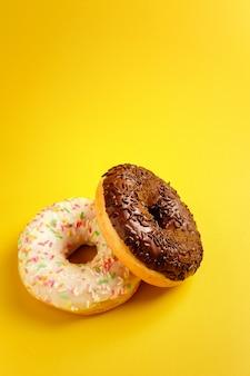 Dois donuts preto e brancos na parede amarela