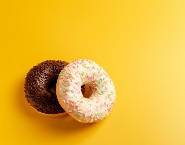Dois donuts preto e brancos na vista superior amarela