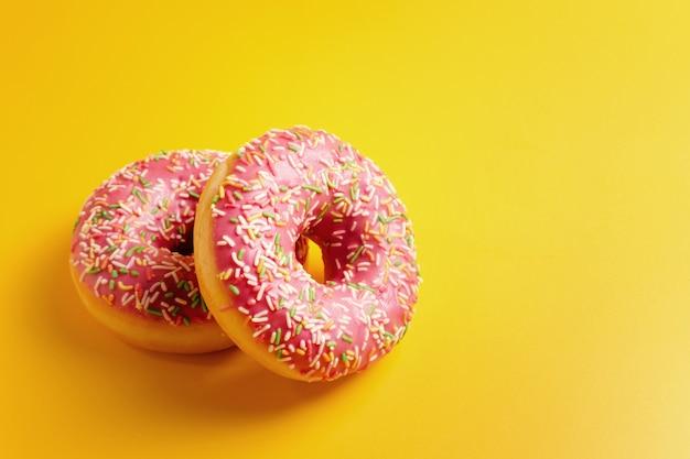 Dois donuts rosa na vista superior amarela cópia espaço