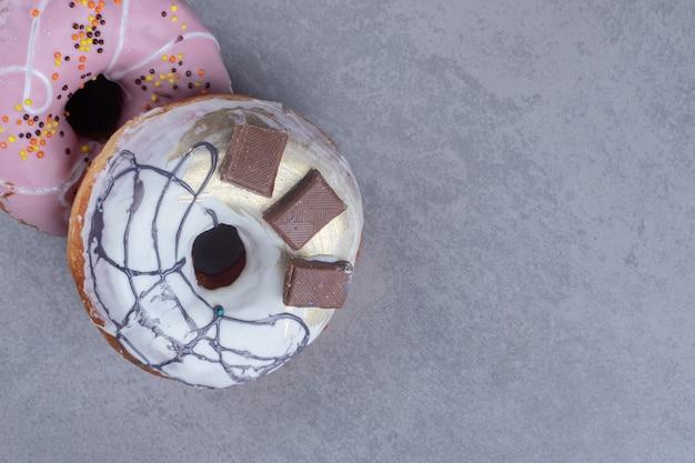 Dois donuts saborosos empacotados juntos na superfície de mármore