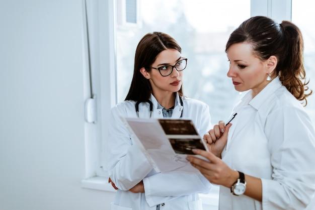 Dois doutores fêmeas sérios que reveem resultados médicos pacientes.