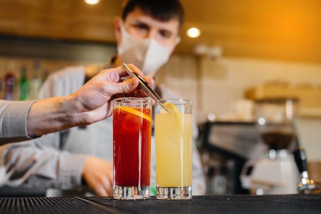 Dois elegantes bartenders com máscaras e uniformes durante a pandemia, preparando coquetéis. o trabalho de restaurantes e cafés durante a pandemia.