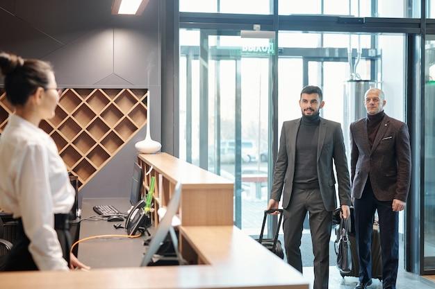Dois elegantes viajantes de negócios com bagagem entrando no saguão do hotel e indo em direção à recepcionista para pedir quarto vazio