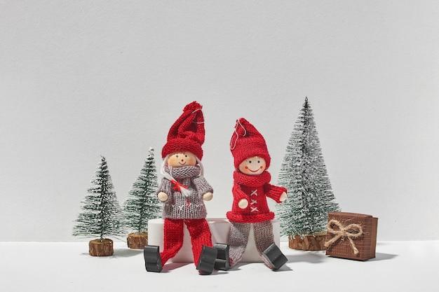 Dois elfos de natal sentados junto com pinheiros e um presente no fundo branco. natal mínimo