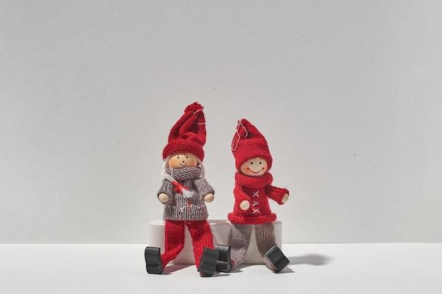 Dois elfos de natal sentados juntos no fundo branco. conceito mínimo de amor no natal