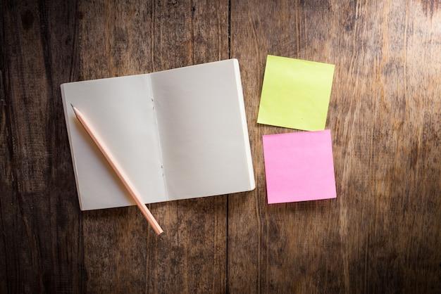 Dois em branco colorido sticky notes e caderno e lápis