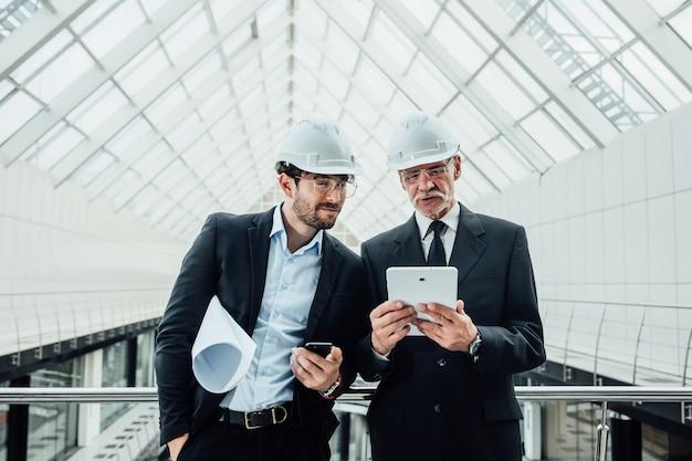 Dois empreendedores de sucesso em um capacete com projeto e laptop de novos edifícios ficam perto de um telhado de vidro