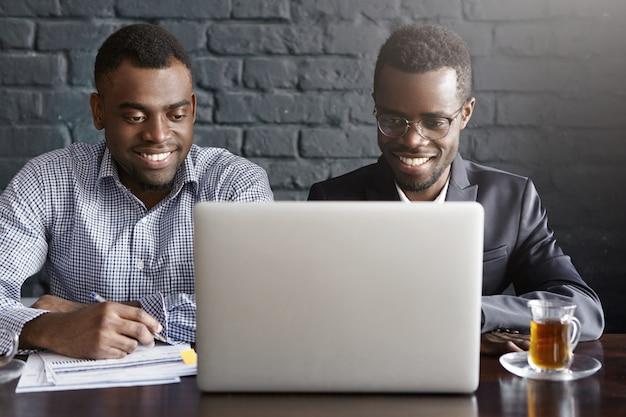 Dois empresários afro-americanos jovens bem sucedidos alegres sentado no interior do escritório moderno na frente do computador portátil aberto, olhando para a tela com um sorriso feliz, discutindo planos de negócios e idéias