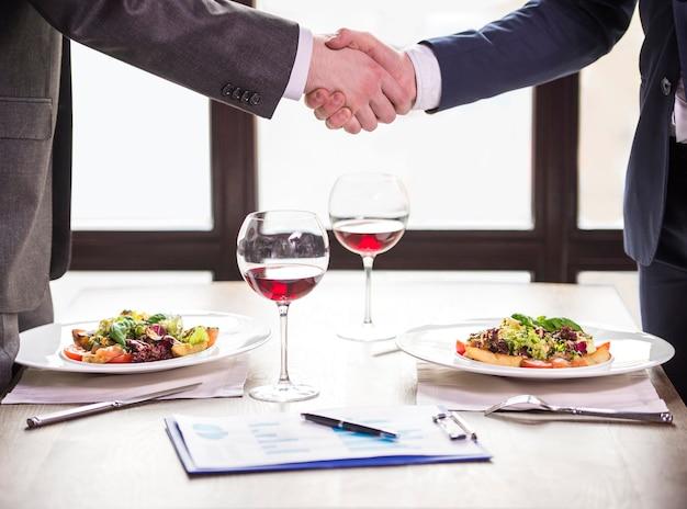 Dois empresários apertando as mãos durante um almoço de negócios.