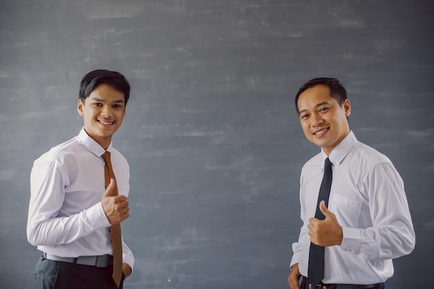 Dois empresários asiáticos de camisa e gravata sorrindo enquanto apontam o polegar para a câmera com espaço de cópia