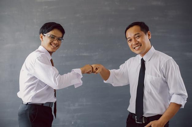 Dois empresários asiáticos de camisa e gravata sorrindo enquanto batem os punhos juntos