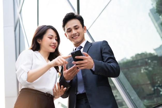Dois empresários asiáticos usando smartphone e conversando