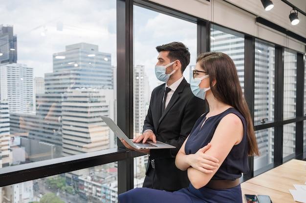 Dois empresários caucasianos usando máscara facial olhando para a cidade e segurando laptop em um novo escritório normal perto da janela
