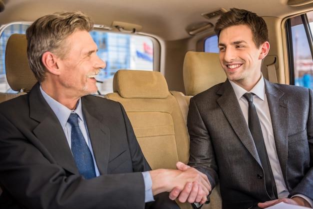 Dois empresários confiantes apertando as mãos e sorrindo.