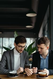 Dois empresários conversando usando um smartphone