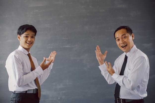 Dois empresários de camisa e gravata sorrindo enquanto se apresentam para o espaço vazio para simulação de negócios