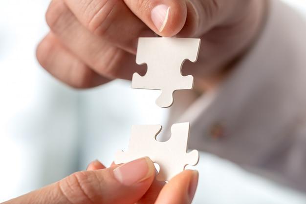 Dois empresários encaixando peças de quebra-cabeça