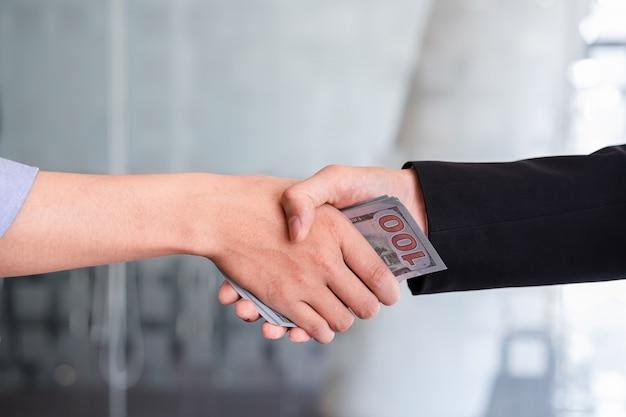 Dois empresários fazendo aperto de mão com dinheiro nas mãos. conceito de corrupção de suborno