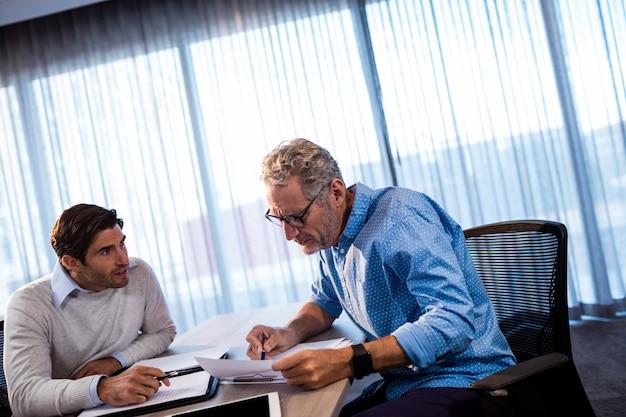 Dois empresários lendo um documento e interagindo