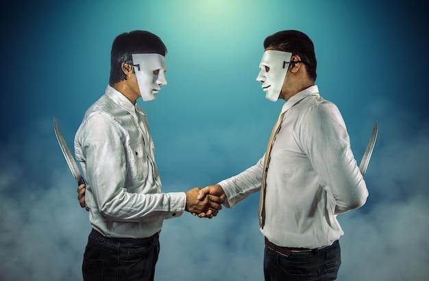 Dois empresários mascarados, apertando as mãos e segurando facas atrás das costas.