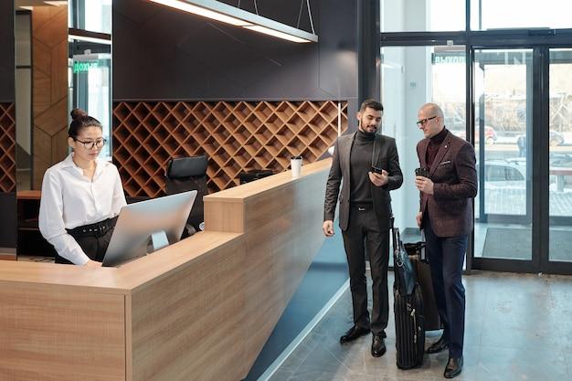 Dois empresários móveis discutindo dados em smartphone enquanto jovem recepcionista usando computador por balcão no saguão do hotel