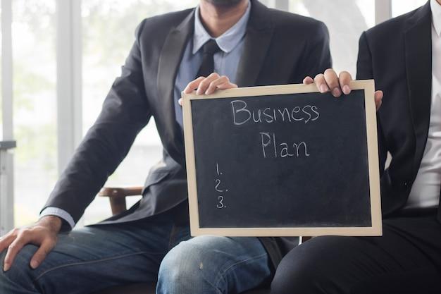 Dois empresários segurando placa preta com palavras passo planejamento, parceiro e conceito de brainstorming