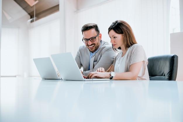 Dois empresários sentados juntos, trabalhando em uma mesa de escritório