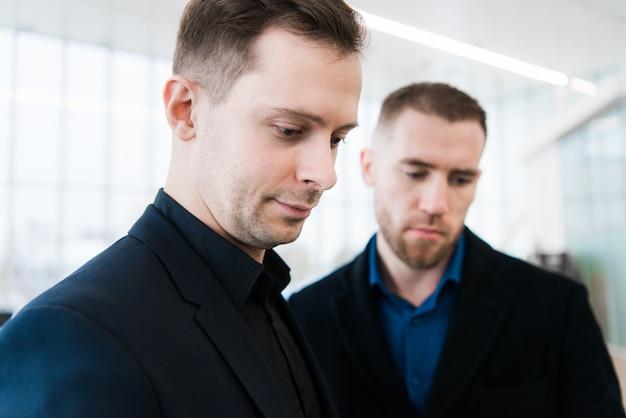 Dois empresários sorridentes no aeroporto, discutindo um projeto importante e olhando para a tela do telefone.