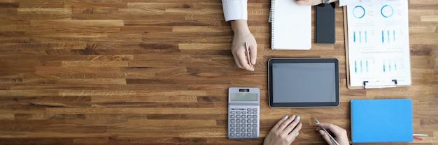 Dois empresários trabalham em ofiice na mesa de madeira